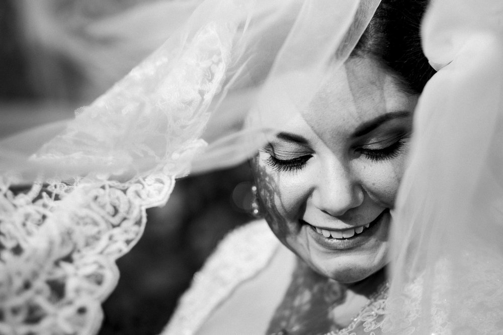Bride smiles through her veil for a portrait session on her wedding day in downtown Toledo, Ohio
