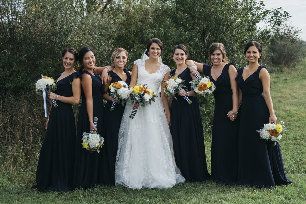 Bridesmaids in their navy blue dresses stand next to bride on her wedding day at Maumee Bay State Park