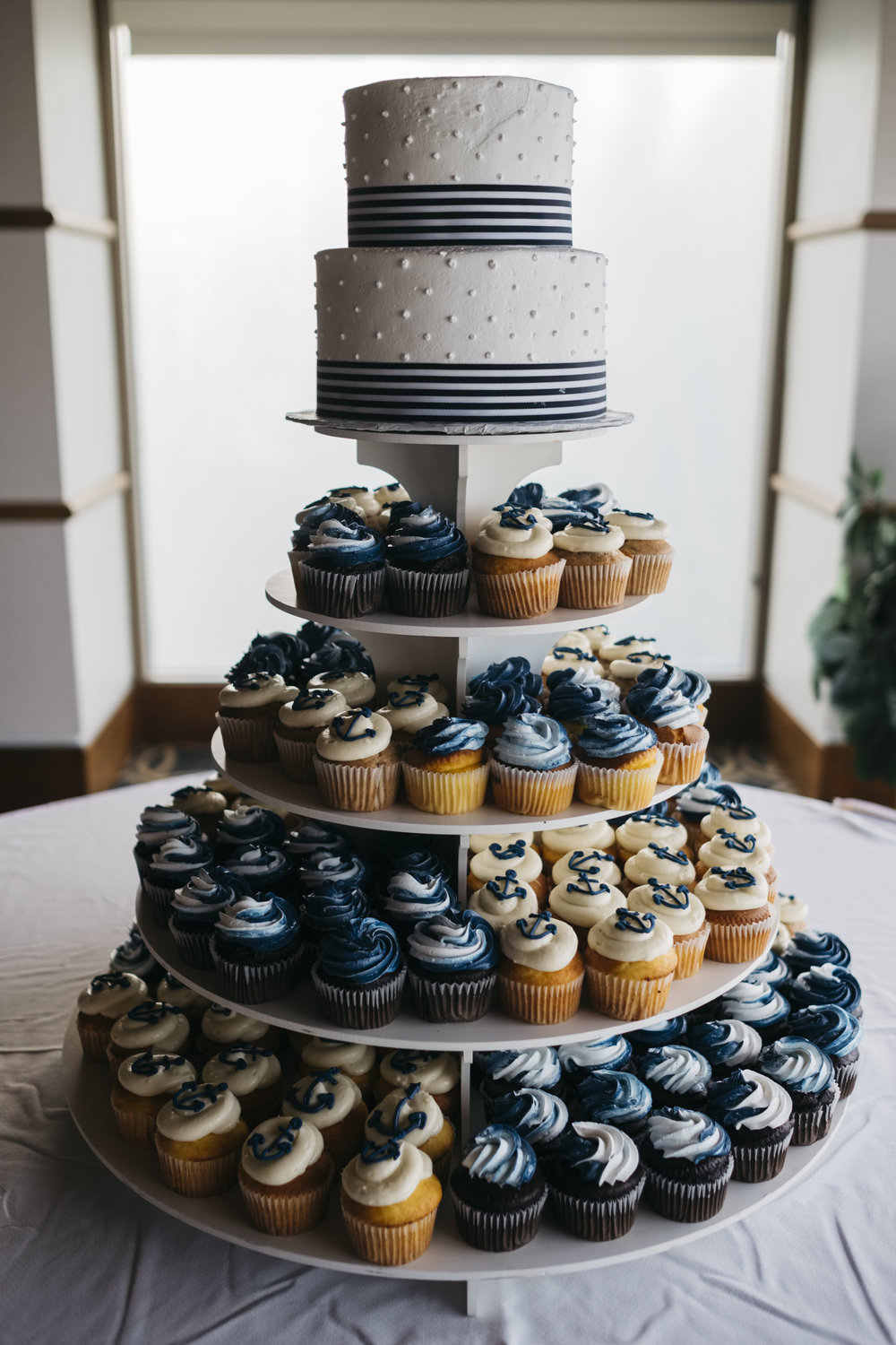 Navy blue and white anchor cupcakes surround wedding cake near Lake Erie wedding reception