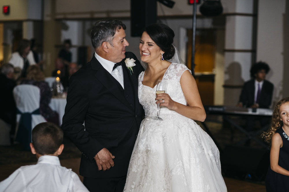 Bride smiles and laughs with her dad at her wedding reception at Maumee Bay State Park