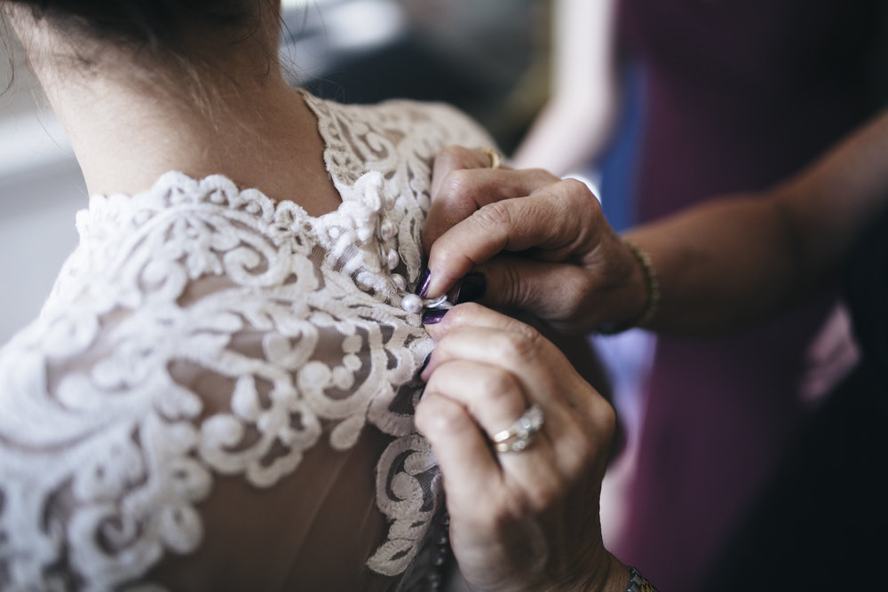 Bride gets her dress buttoned up by her mother before her wedding ceremony on BGSU's campus