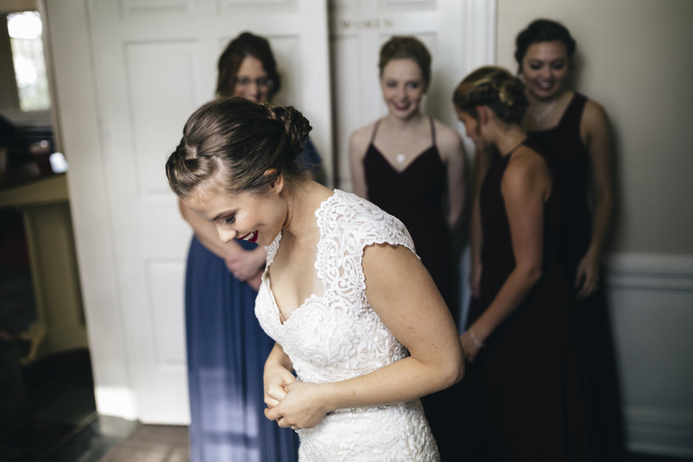 Bride smiles with her bridesmaids surrounding her before her wedding ceremony at BGSU