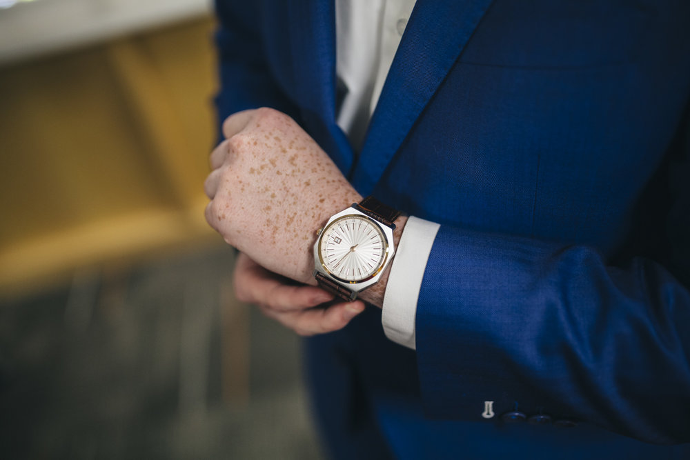 Groom puts on his watch before his wedding