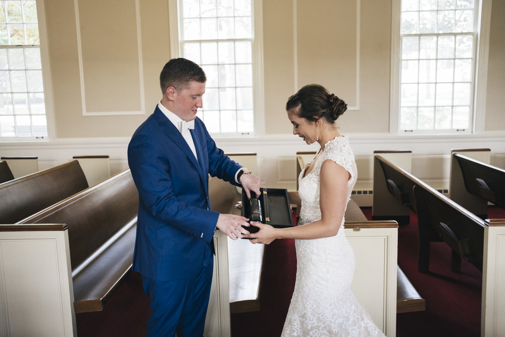 Bride and groom put wine in a box that they will save for their one year anniversary