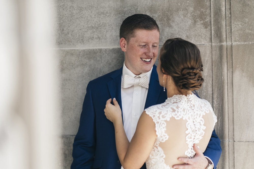 Bride and groom share an intimate moment before their wedding ceremony laughing and smiling under an archway on BGSU's campus
