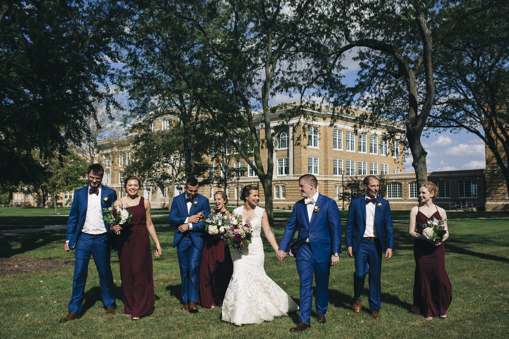 The bride and groom walk on BGSU's campus with their bridal party