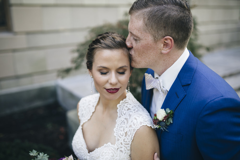The groom kisses his bride's forehead in an intimate moment before their wedding ceremony