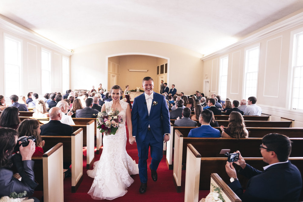 Bride and groom leave Prout Chapel at their BGSU Falcon Flame wedding
