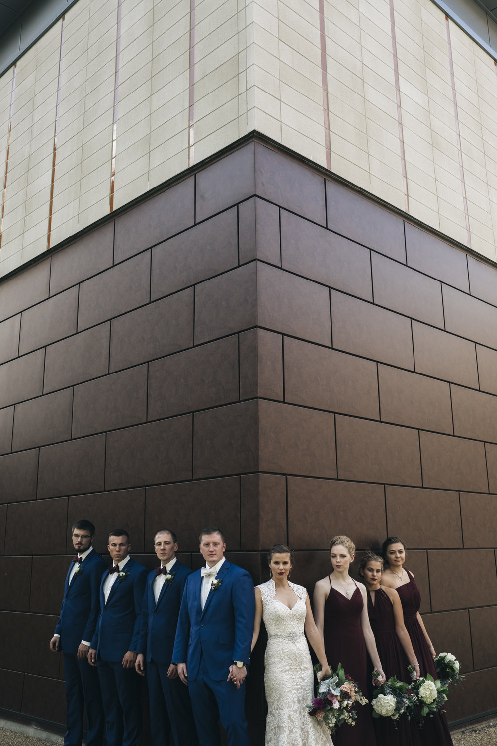 Bridal party stands against wall on BGSU campus before wedding reception