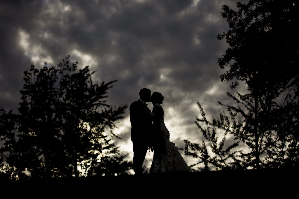 Bride and groom silhouette kissing outside of Belmont Country Club in Northwest Ohio