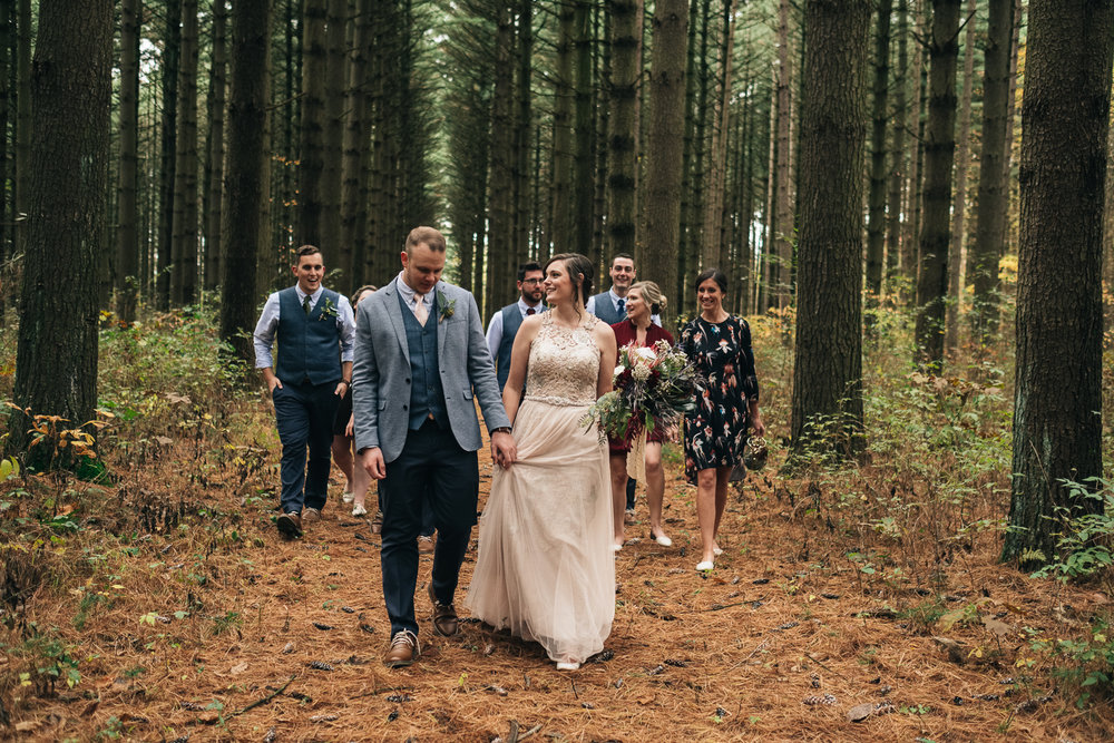 Bride and groom walk through the woods during their fall wedding in Northwest Ohio