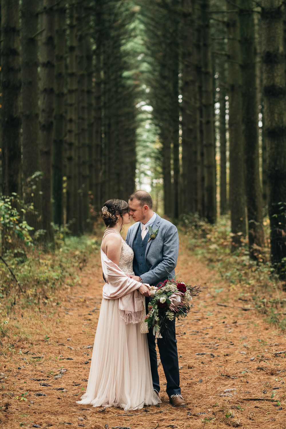 The bride stands at Oak Openings in her custom designed wedding dress from Belle Amour Bridal in Toledo