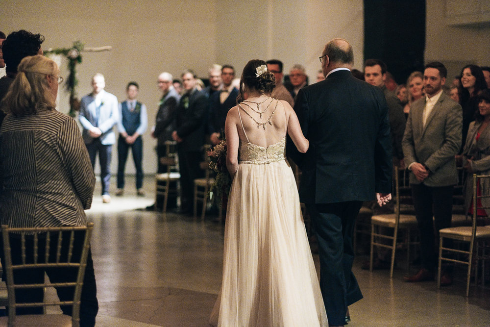 The father of the bride walks her down the aisle at her wedding ceremony in late October wedding in Toledo