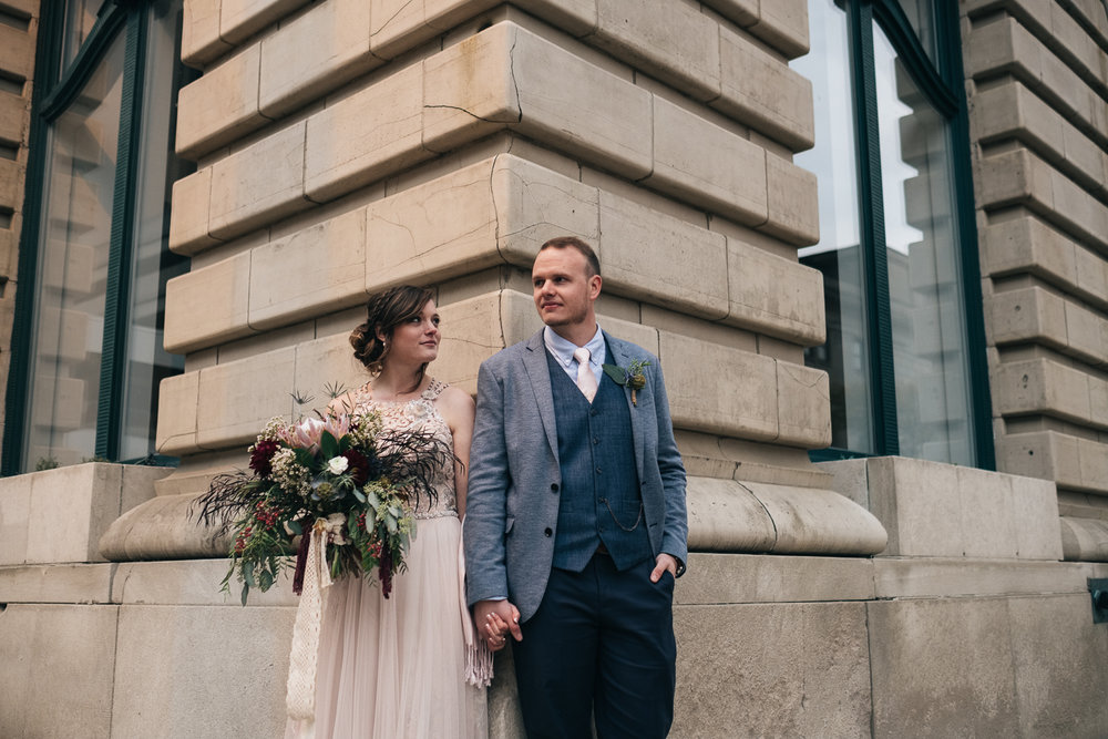 Bride and groom stand outside of Registry Bistro for their wedding photos in late October