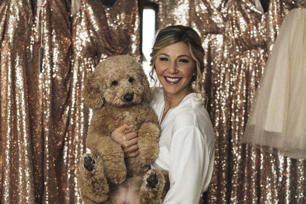 Bride with dog getting ready on weddign day.