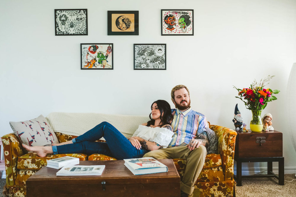 Couple sits on couch during in home engagement session