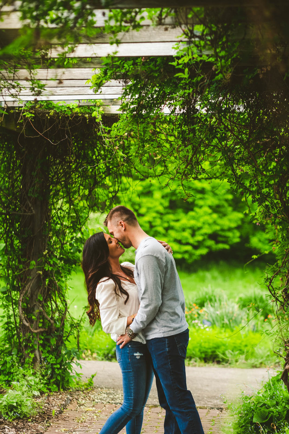 Couple Stands Under Trellis for Toledo Botanical Garden Engagement Session