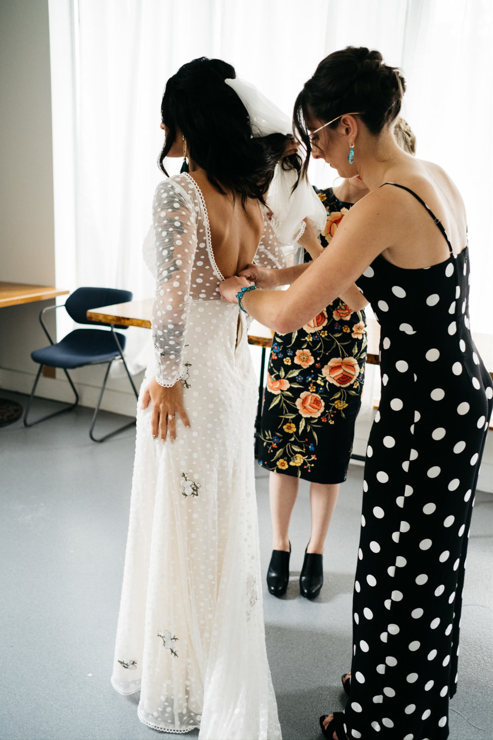 Bride Gets into Dress before Ceremony at Growing Hope Market Place with Destination Wedding Photographers from Toledo
