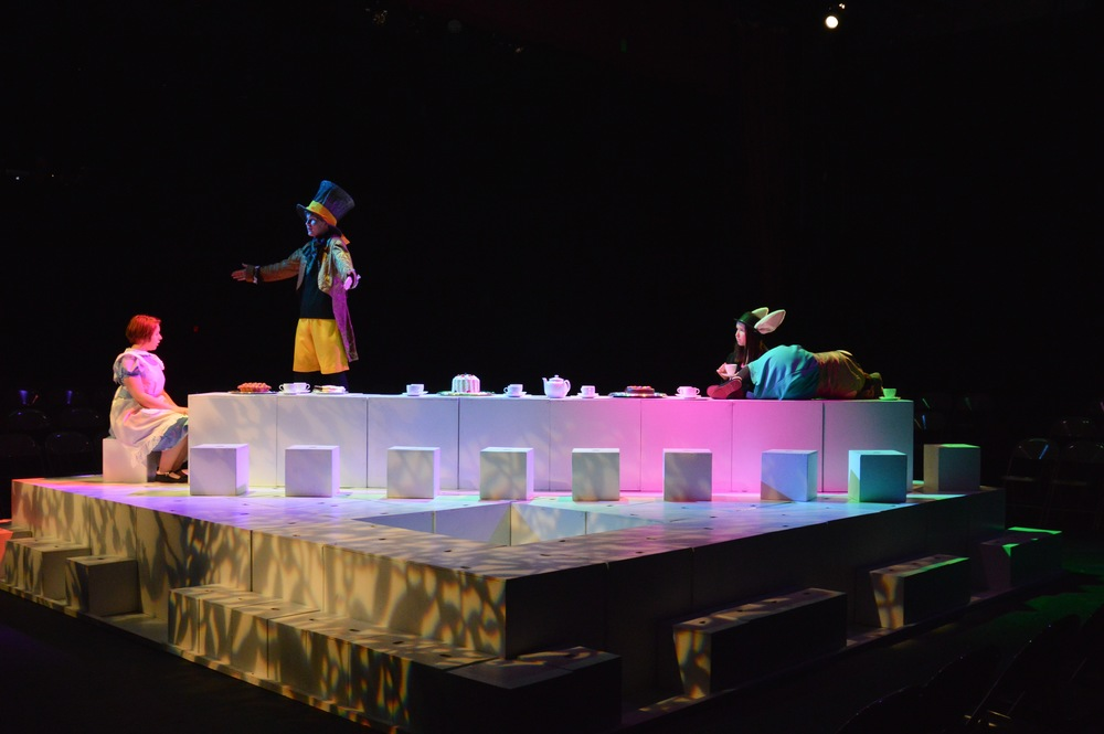 OUR SET CONSISTS OF 128 WHITE CUBES WHICH ARE UTILIZED IN VARIOUS WAYS TO DEPICT ALL THE LOCATIONS AND ELEMENTS OF WONDERLAND. CHARLES DODGSON WAS A UNIVERSITY PROFESSOR OF MATHEMATICS WHICH ACCOUNTS FOR THE HUGE ROLE LOGIC AND NUMBER PUZZLES PLAY IN THE BOOK. OUR GEOMETRIC SCENIC DESIGN IS A TRIBUTE NOT ONLY TO THIS MATHEMATICAL ELEMENT BUT ALSO TO THE IMPORTANCE OF IMAGINATION AND INVENTION IN ALL OF ALICE'S ADVENTURES.