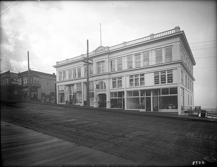 "Mrs. Upper's Barber Shop was located in the second building to the left of the White House Building in this picture. The small building directly to the left of the White House is now Fourth Corner Frames. In the later 20s, the upstairs was known as the ""Tama Rooms,"" a popular spot to which the police were called regularly but was allowed to operate as a brothel for over a decade."