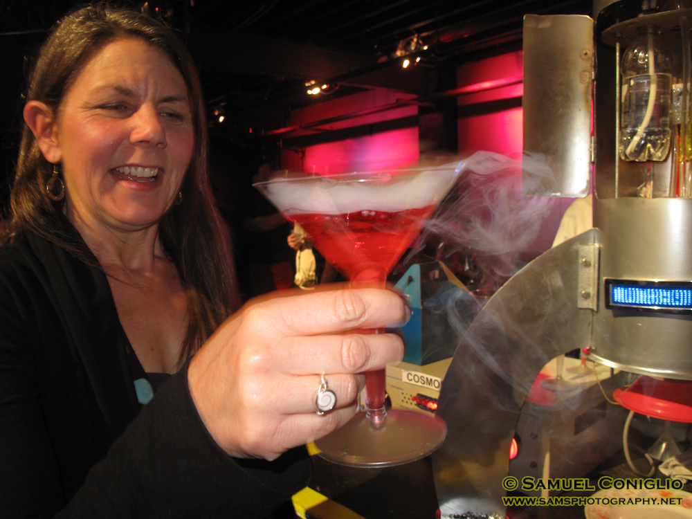 A happy customer enjoys her cosmic cocktail created by the COSMOBOT!