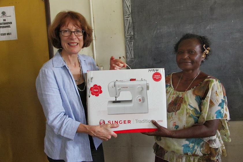 Australia High Commissioner Deborah Stokes presents sewing machines to a local women's group.