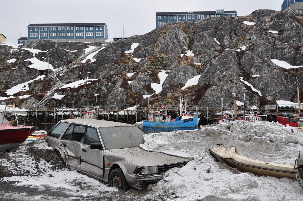Vår i Nuuk. En bil dukker opp under snøen.
