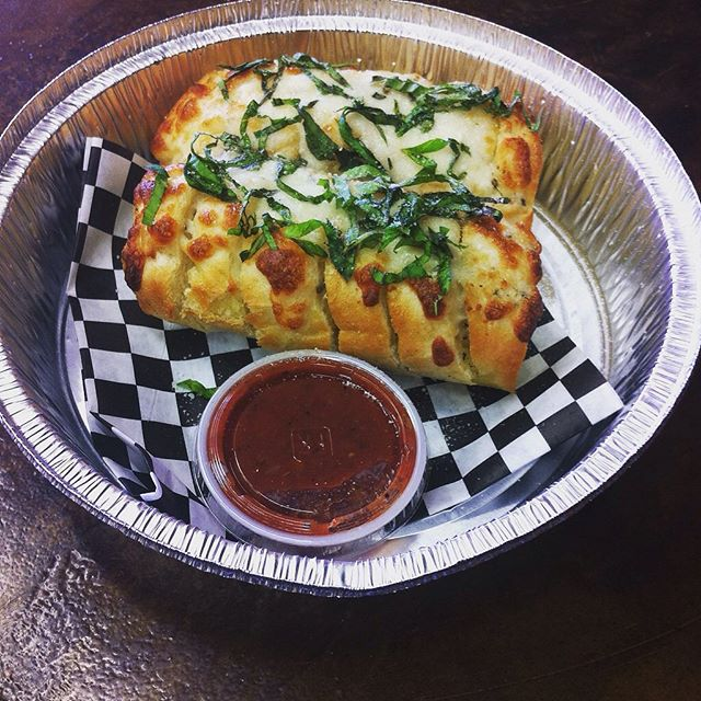 Have you tried our baguette? It is stuffed with garlic butter and topped with basil! You can also add cheese and/or jalapeños. It is great on its own or paired with lasagna. #pizza #fullerton #orangecounty