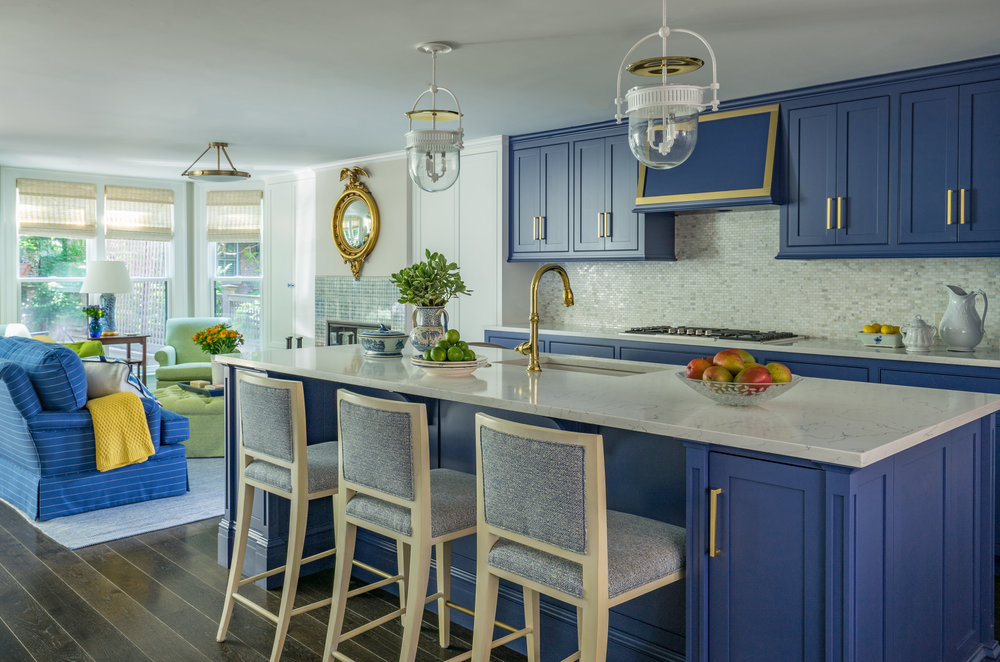 """""""The interior rooms have been designed in keeping with those of a South End single-family row house built in 1899—with the twenty-first-century upgrades needed to adapt to the needs of a modern family."""" Custom cabinetry painted      Farrow & Ball      Drawing Room Blue with brass hardware/fixtures. Counter Stools by      Kravet     , Lights by      Urban Electric Company     ."""