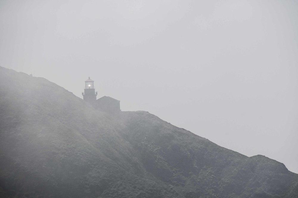 A lighthouse shines through the mist.