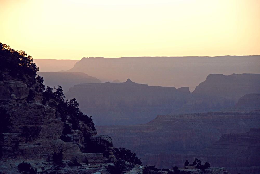 Cliffs recede into the sunset haze.
