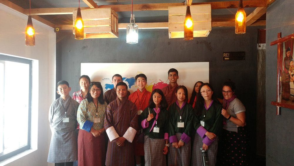 "The ""Media"" group learns about public television from popular travelogue show host, Sangye Choiphel (third from left, front row), at the hip ""Café Incomplete"" in downtown Thimphu. His show, Nazhoen Express, educates Bhutanese about the rich culture of their own country and has given people from around Bhutan a sense of pride about their small villages and distinctive cultural practices. (Mme Deki, ELC Principal extraordinaire, second from left!) (Students, from L to R: Sonam, Skylar, Alex, David, Samara, Ishaan, Kunchok, Miraya, Choiying; plus Ms. Staffaroni!)"