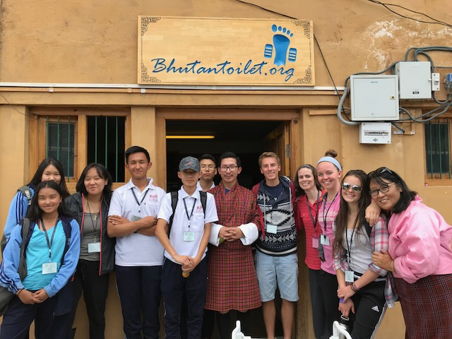 "The ""Environment"" group visits the Bhutan Toilet Organization to become inspired about the importance of access to clean toilets. In the center, director Passu Tshering spoke of his passion for his work, after changing careers from being a science teacher to directing this important effort. (From L to R: Menday, Trisha, Tenzin, Rabsel, Karma, Tashi, Mr. Passu, Hugo, Ms. Strong, Kelly, Claudine, Mme. Deki.)"