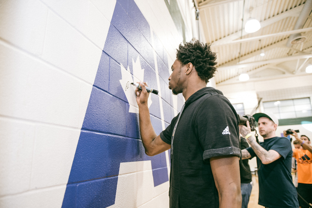 Andrew Wiggins signs his newly unveiled logo at the Dufferin Clark Community Centre gym