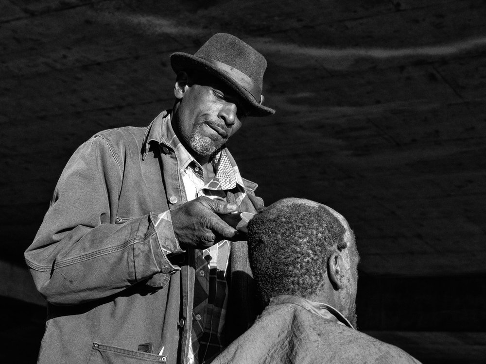 """Gino """"the barber"""" cutting his brothers hair in a homeless camp. When Gino was born his mother was 13."""