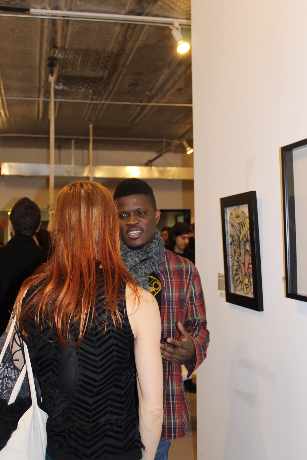 Laolu discusses his art with one of the guests.