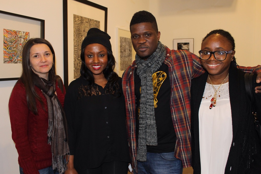 Laolu poses with Dorina, Njeri, and Onyew at the event with his art pieces providing the background.