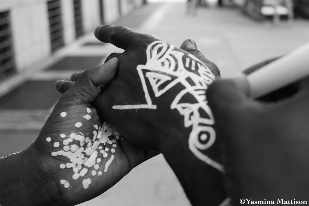 Laolu paints the hand of babalawo and friend Afolabi outside of Columbia. (Photo by @yasminamattison)