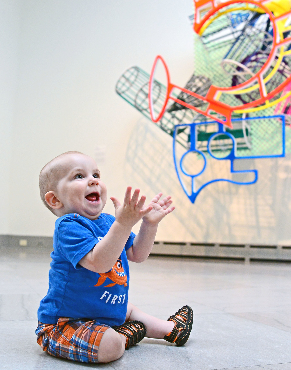 A small child sits on the floor, his two teeth exposed in a gleeful grin as he reaches up toward a colorful sculpture