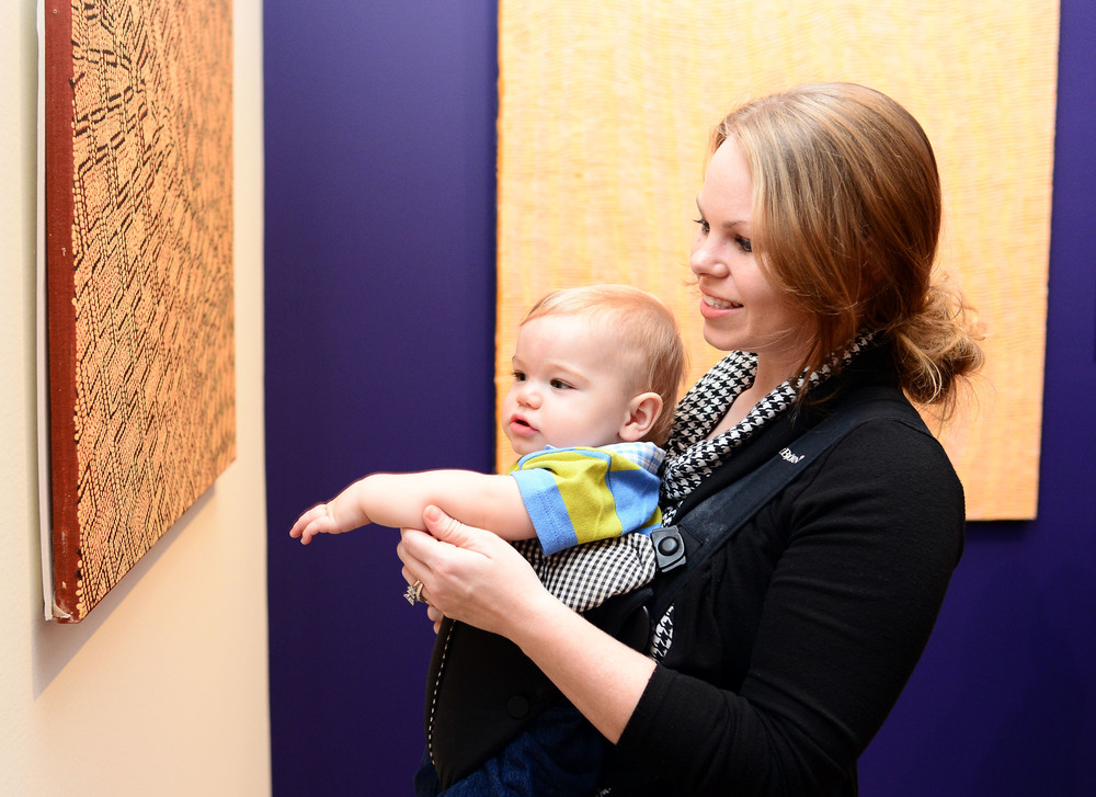 A woman holds a baby in a sling on her chest, guiding his arm toward a painting on the wall in front of him