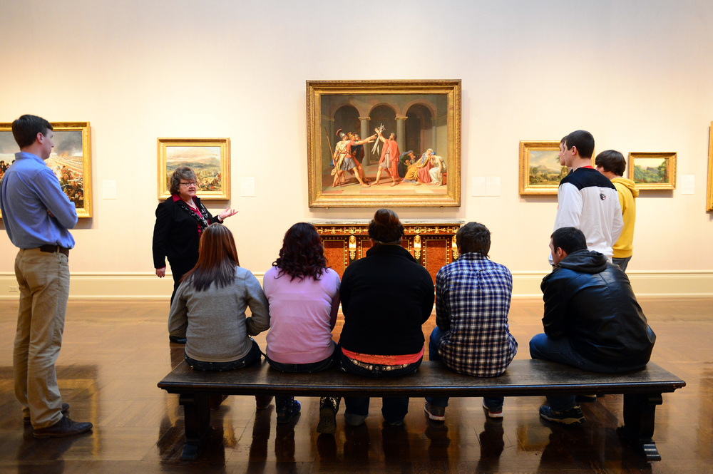 5 high schoolers sit on a bench and observe a painting on a wall in the museum