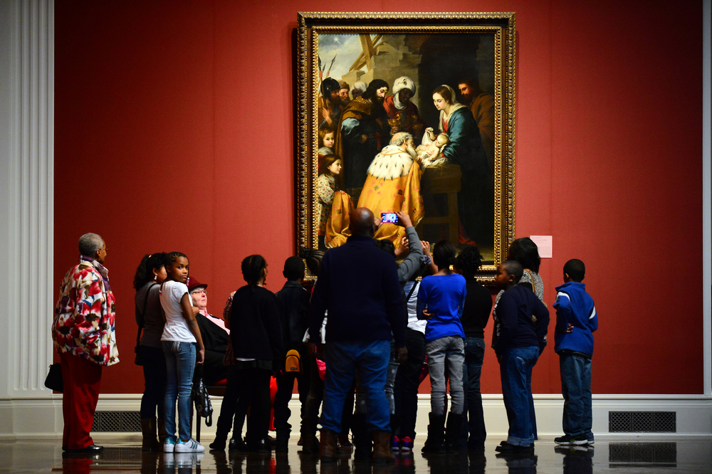 A group of middle schoolers and teachers stand in front of a large painting hanging on a wall in the museum