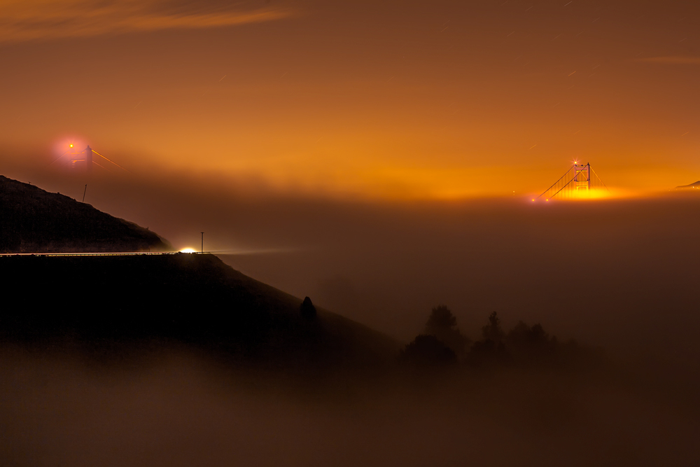 The city of San Francisco shines bright far away in the morning fog.