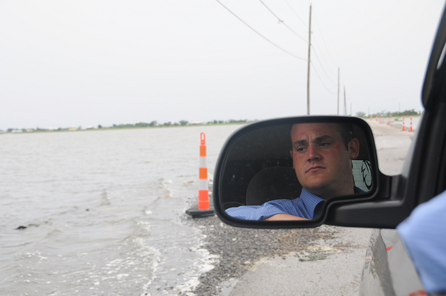 Photo by Rainforest Action Network  / Creative Commons. Chris Chaisson of the United Houma Nation eyes the waves as water covers half the road to Isle de Jean Charles in the Louisiana bayou.