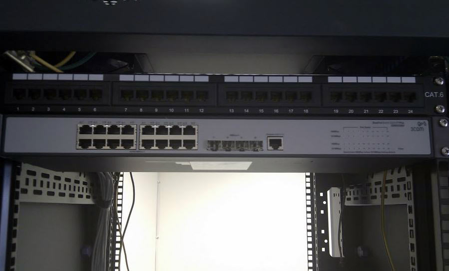 Upper part of rack showing patch panel and switch.