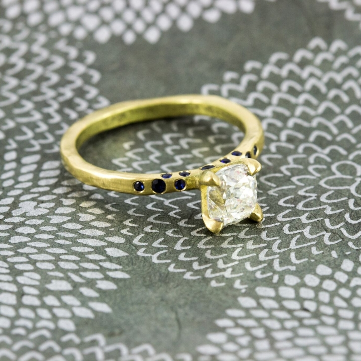 18k Yellow gold with 1.06 cushion mine cut diamond. With natural colored sapphires.