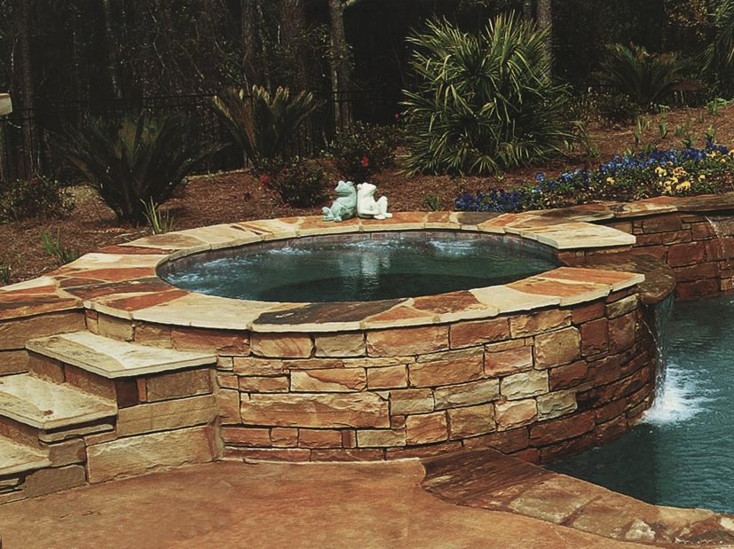 Raised spa wall with natural stone veneer and 6x6 waterline tile. Mosiac stone coping and Hydrazzo interior finish.