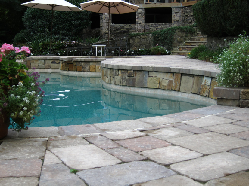 Tri-State project with Canyon Creek stone veneer finishing the raised bond beam. Tumbled Paver coping with Pebble Tec interior finish, Sandy Beach. Tumbled Paver deck, Mega-Bergerac.