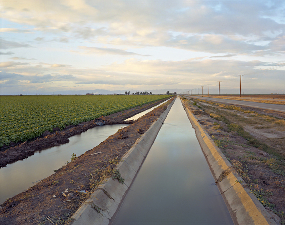 "Irrigation Canal, Imperial Valley near Westmoreland, CA, 2013    The vast Imperial Irrigation District includes over 1,400 miles of canal and 1,100 miles of pipeline.  This elaborately constructed system also conveys surface runoff and subsurface drainage from fields to the Salton Sea, which is a ""designated repository for agricultural runoff with environmental considerations not yet solved."""