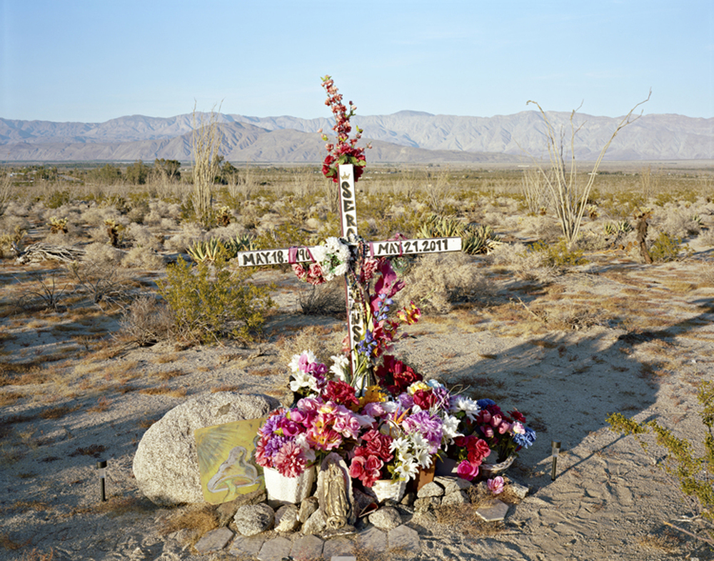 Descansas en Paz, near Borrego Springs, CA, 2013 A Shrine for Sergio Sanson is one of many similar sites in the area marking roadside fatalities.  This same arid landscape also bears the footprints of the many undocumented people crossing from Mexico to United States in search of jobs and a better life.  One humanitarian group services 150 water stations from March to October each year in an effort to stem the number of deaths from dehydration that occur in the Imperial Valley.